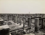 Field Museum construction site photograph of a single figure standing near barrel tube amongst the...