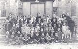 Photo of a large group of children and two teachers standing and sitting on the steps in front of a brick building.