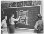 Three Students Working On A Blackboard Crossword Puzzle