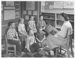 Junior High Student Reading to Young Students 1955