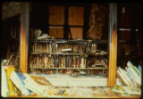 Bookcases, books, a wall, and a door frame charred as a result of the April 19, 1989 firebombing...