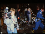Joliet Fire Department personnel, a Joliet Police officer, and a news videographer at the scene of...